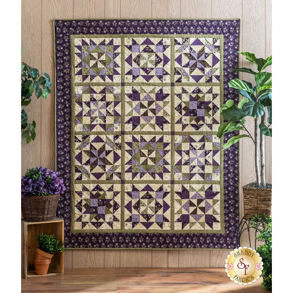 The beautiful finished Clover Meadow quilt displayed hanging on a wall