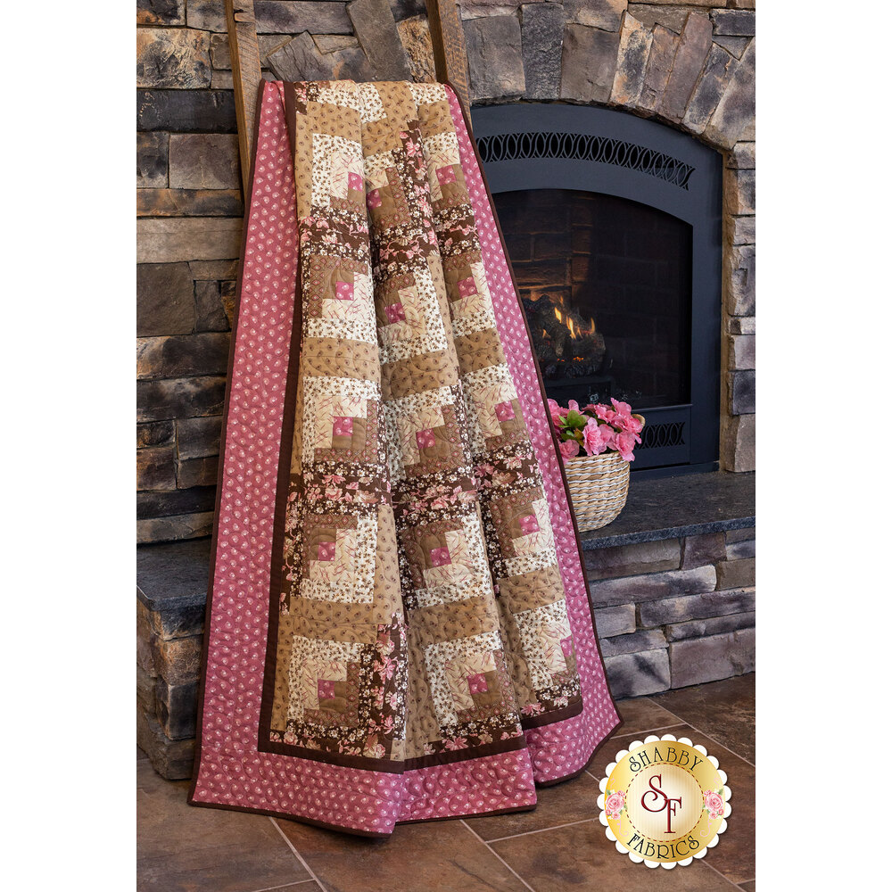 Brown and tan log-cabin block pieced quilt with a rose pink border draped near a fireplace.