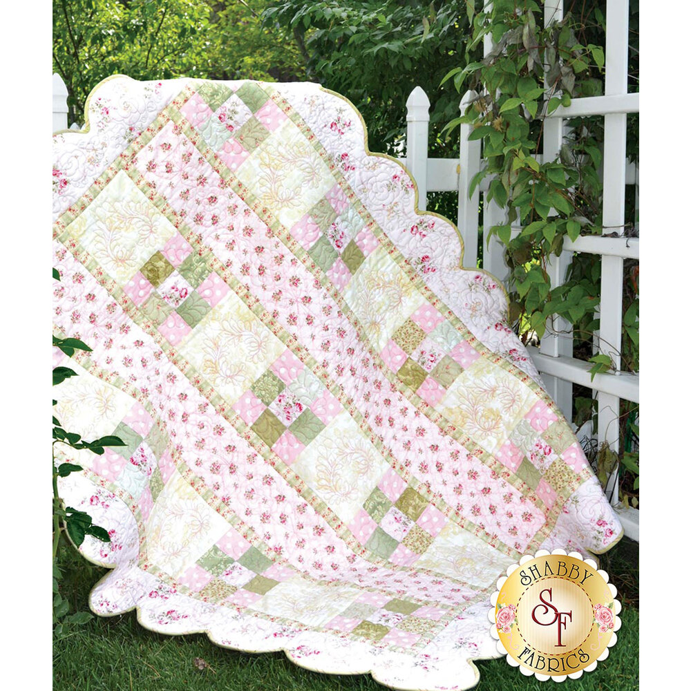 Pastel quilt with pink 9-patch blocks, ivory blocks, and scalloped borders.