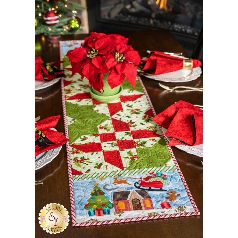 The Christmas themed Easy Pieced Table Runner for December displayed on a table