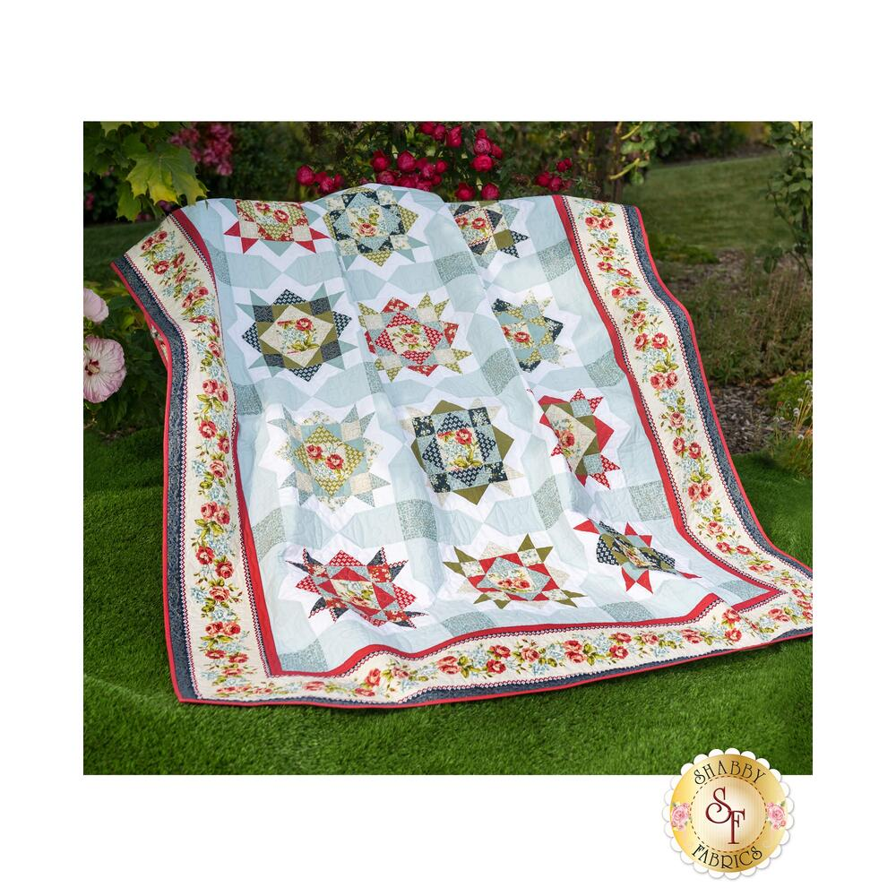 A beautiful summer quilt with Enchanted Garden fabrics displayed on a wall
