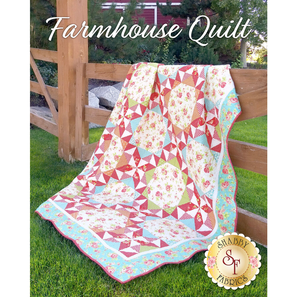 Red and teal geometric quilt draped over a rustic wooden fence.