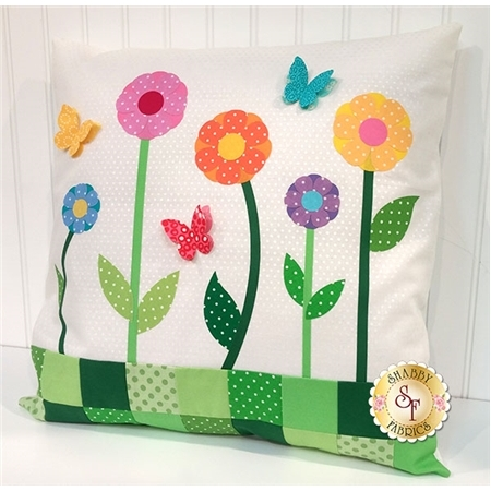 White polka-dotted pillow with colorful flower and butterfly applique shapes.