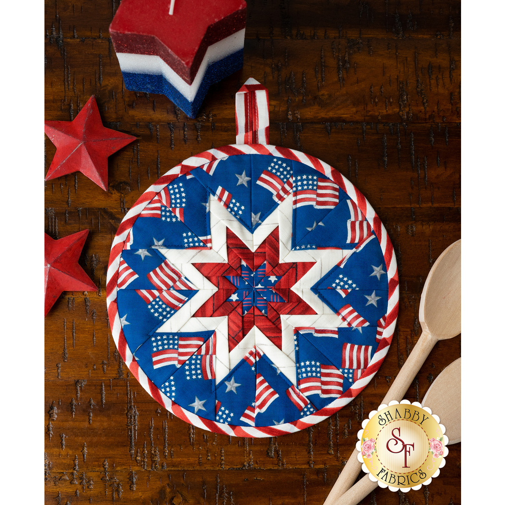 Blue folded star hot pad with tossed American Flags on a wood table