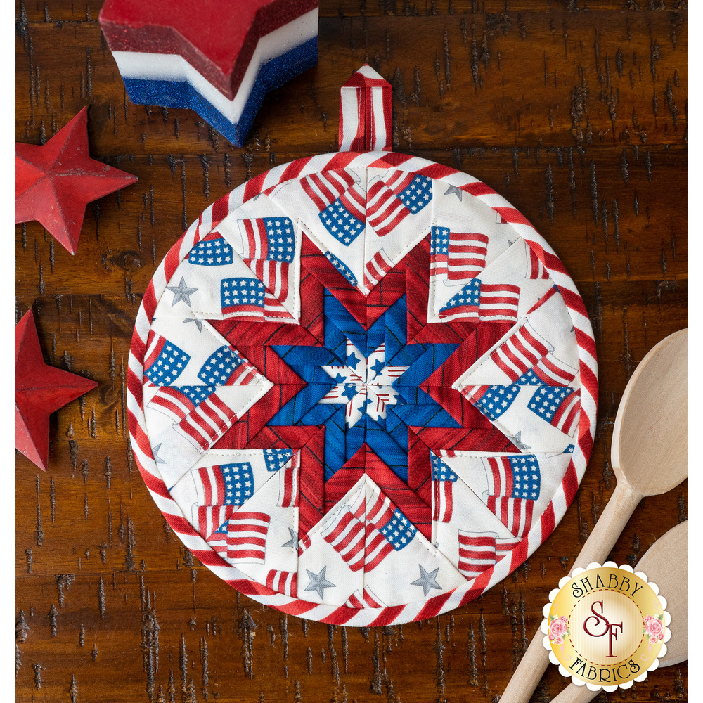 Patriotic hot pad made with America the Beautiful fabrics on a wood table