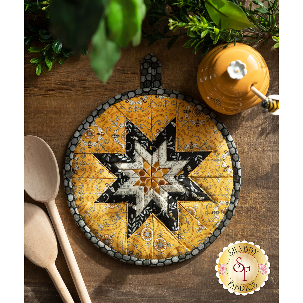 Yellow, black, and cream Folded Star Hot Pad laid flat on a wood table