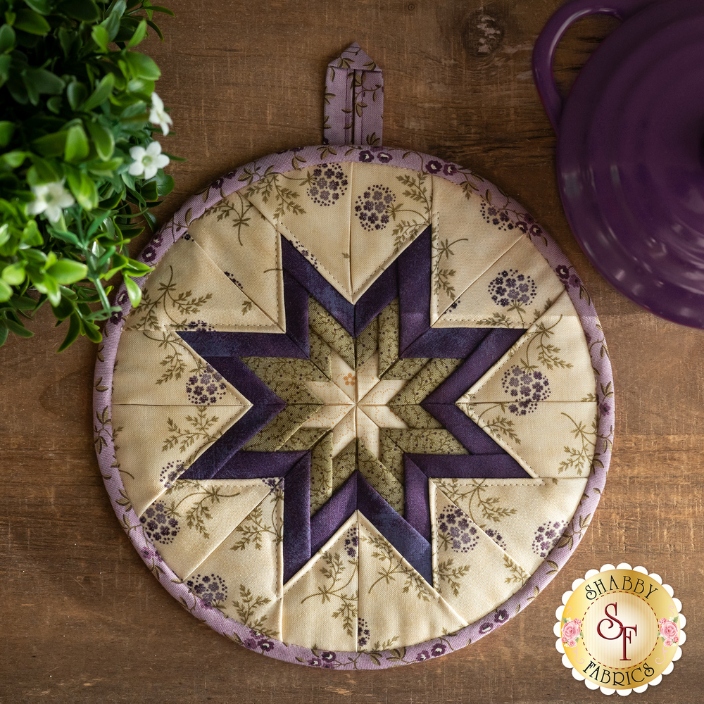 The Clover Meadow Folded Star Hot Pad in cream laid flat on a wood table
