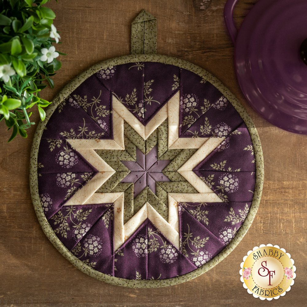 The Clover Meadow Folded Star Hot Pad in purple laid flat on a wood desk