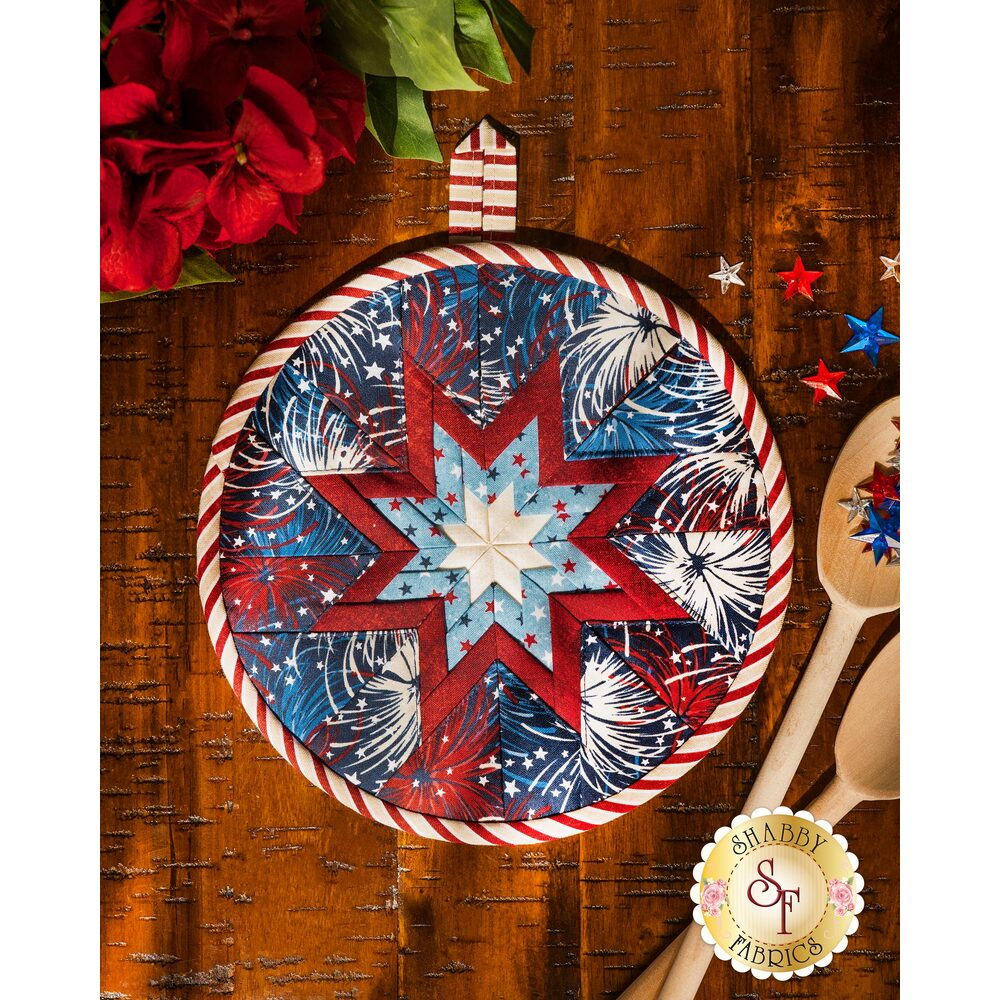Patriotic themed hot pad with fireworks laid flat on a wood table