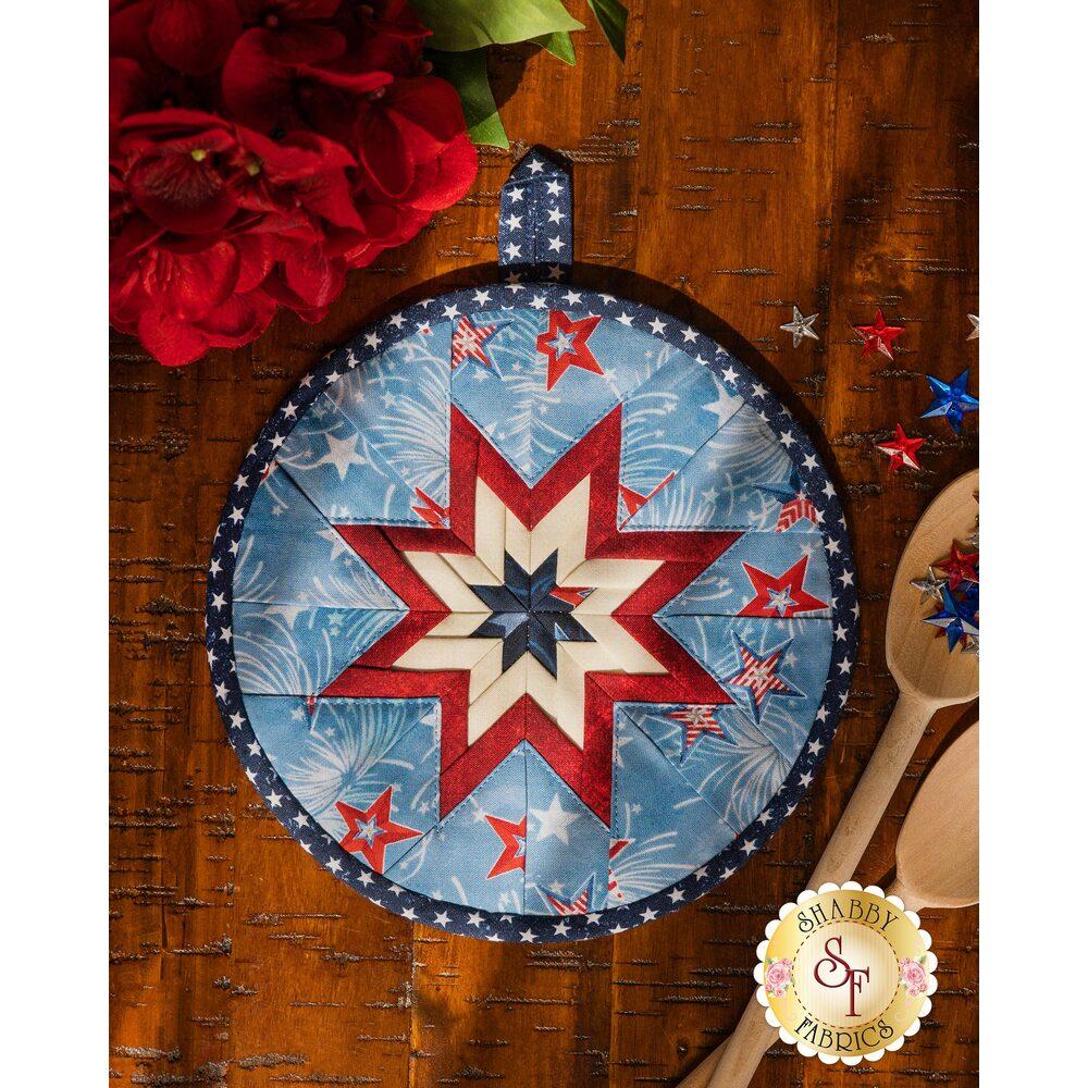 Light blue patriotic Folded Star Hot Pad laid flat on a wood table