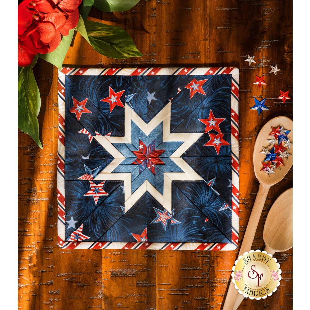 The dark blue Liberty Lane Folded Star Squared Hot Pad on a brown wood table