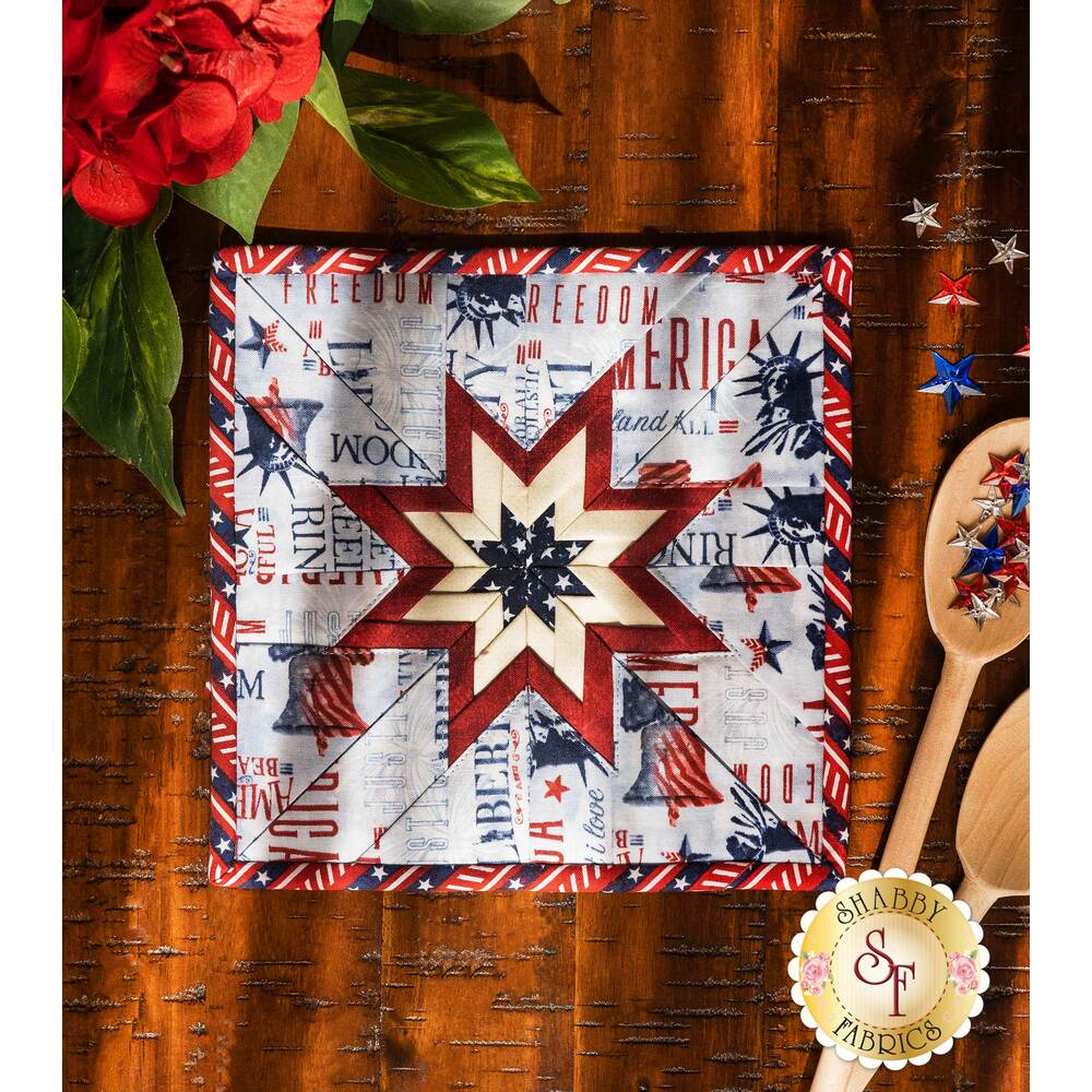 The light blue Liberty Lane Folded Star Squared Hot Pad on a brown wood table