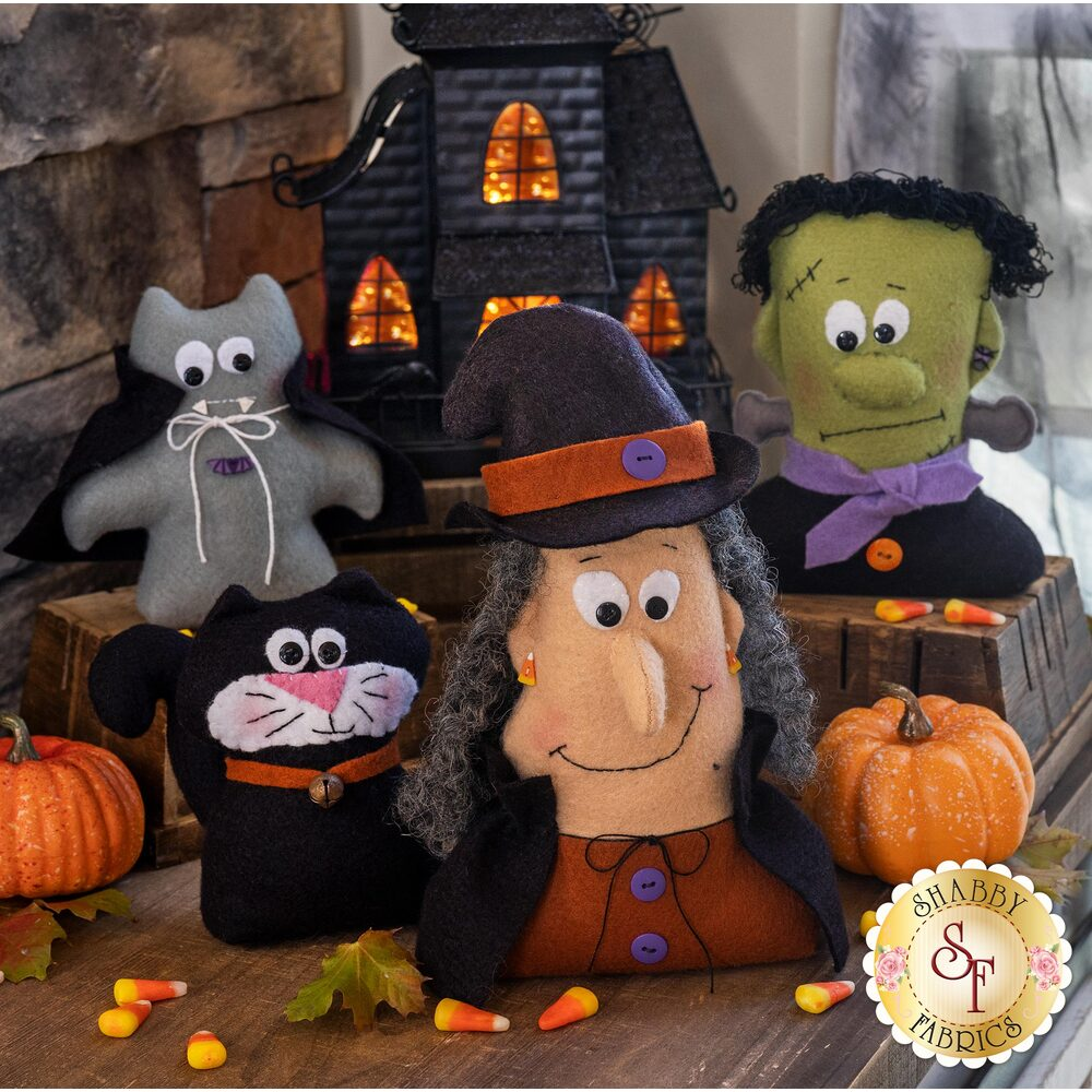 4 Wool felt characters - A black cat, Frakenstein, a witch, and vampire in front of a haunted house