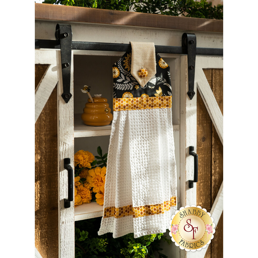 A yellow, black, and cream themed Hanging Towel hung from a cabinet
