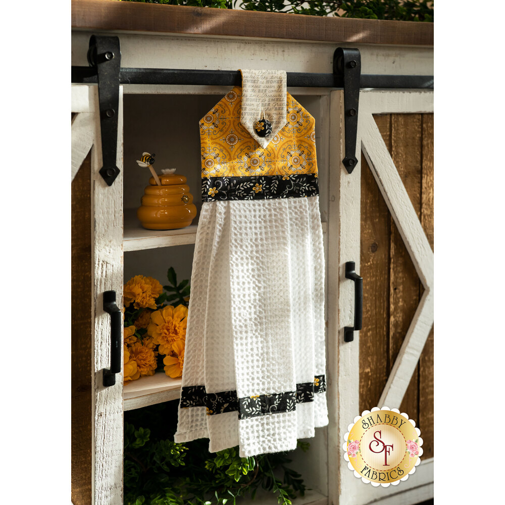 A yellow, white and black Hanging Towel hung from a cabinet