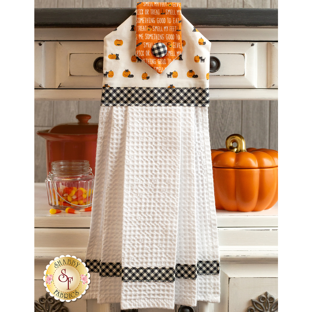 White and orange Halloween towel hanging from a cabinet