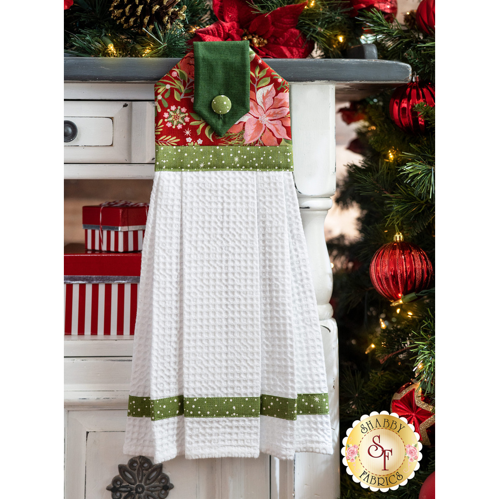 Red and green towel with white waffle weave toweling hung from a cabinet