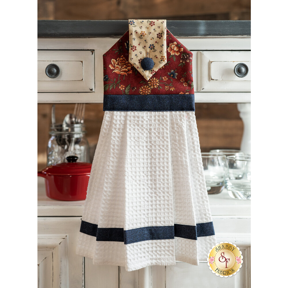 The Through the Years Hanging Towel displayed in front of a cabinet | Shabby Fabrics