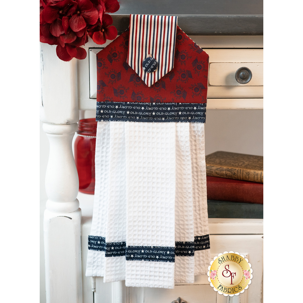 The beautiful patriotic themed hanging towel hung from a cabinet
