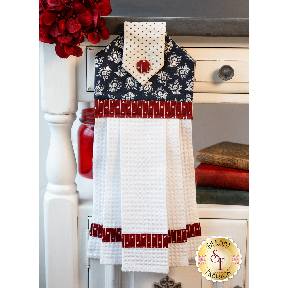 A beautiful patriotic themed hanging towel hung from a cabinet