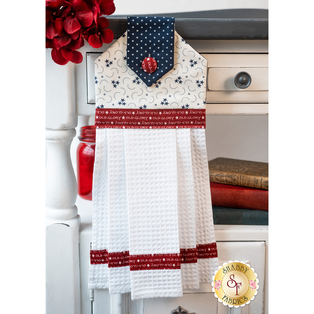 A beautiful red, white, and blue hanging towel hung from a cabinet