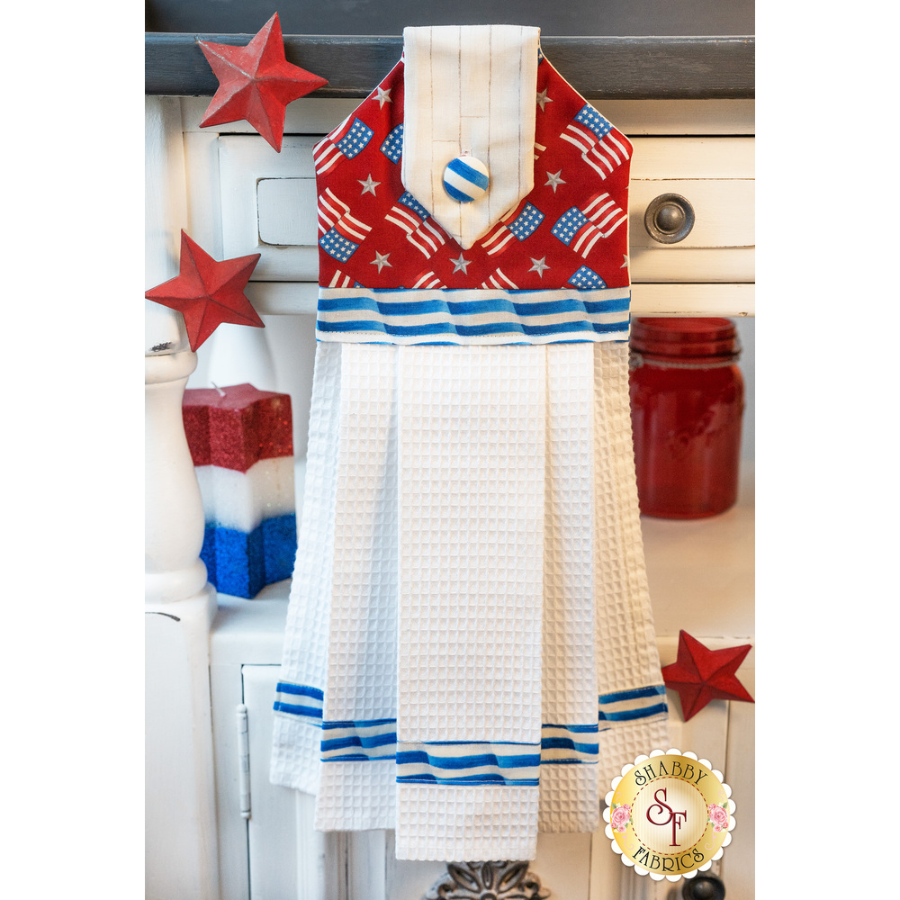 Patriotic red, white, and blue hanging towel hung from a cabinet