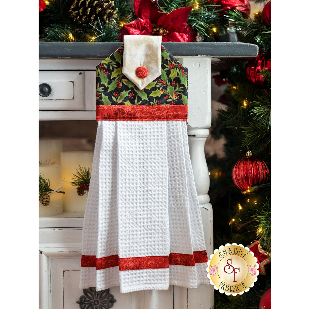A beautiful black, cream, and red Christmas hanging towel hung from a cabinet