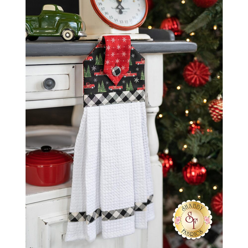 Black and red Christmas themed hanging towel displayed on a cabinet