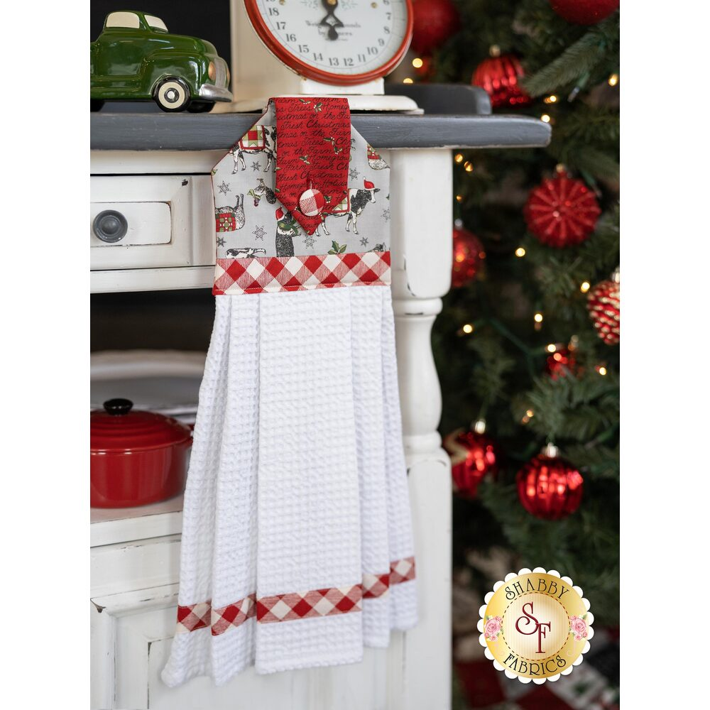 A gray and red Christmas themed hanging towel hung from a cabinet
