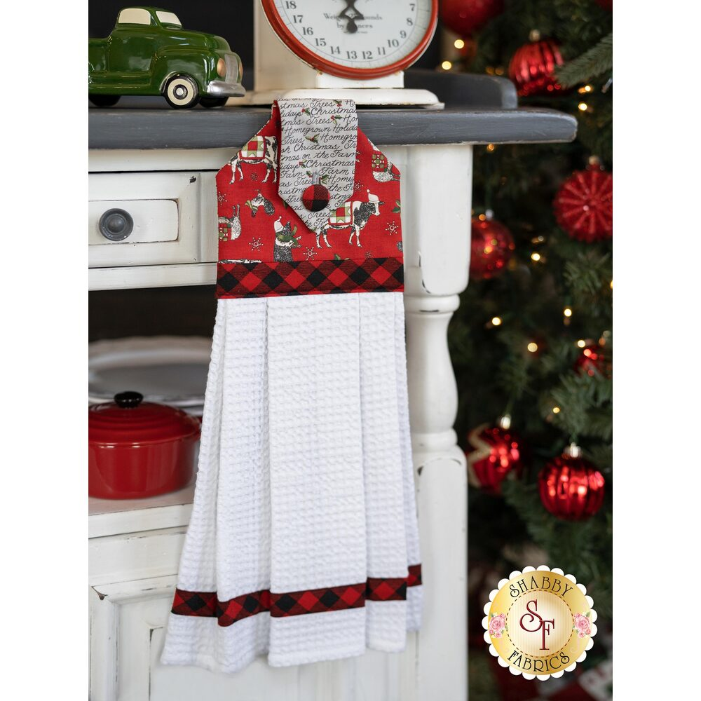 Red and gray themed hanging towel displayed hanging from a cabinet