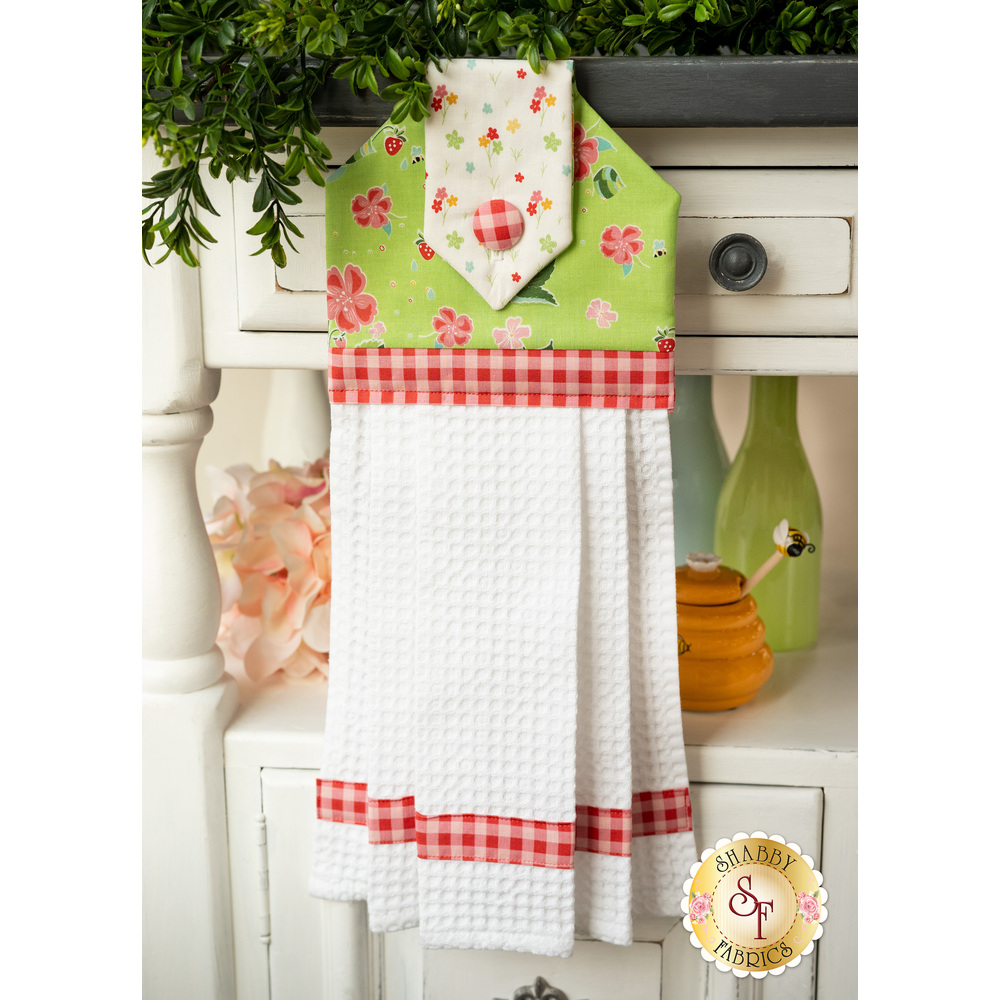 Greed, pink, and white waffle weave hanging towel hung on a cabinet