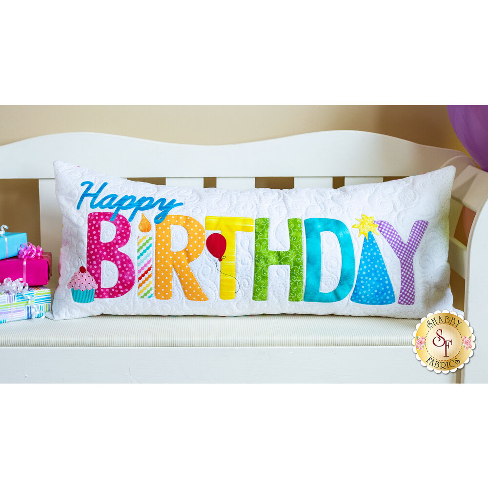 Happy Birthday Pillow with a brightly-colored rainbow of applique letters, resting on a white bench.