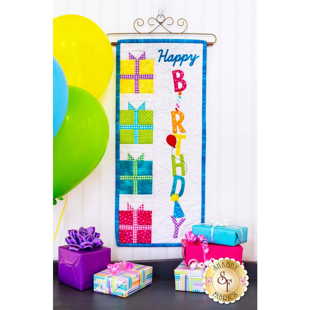 Wall hanging reading Happy Birthday with yellow, green, blue, and pink gift blocks.