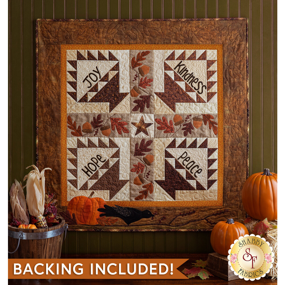 Beautiful autumn quilt with 4 blocks hanging on a green wall