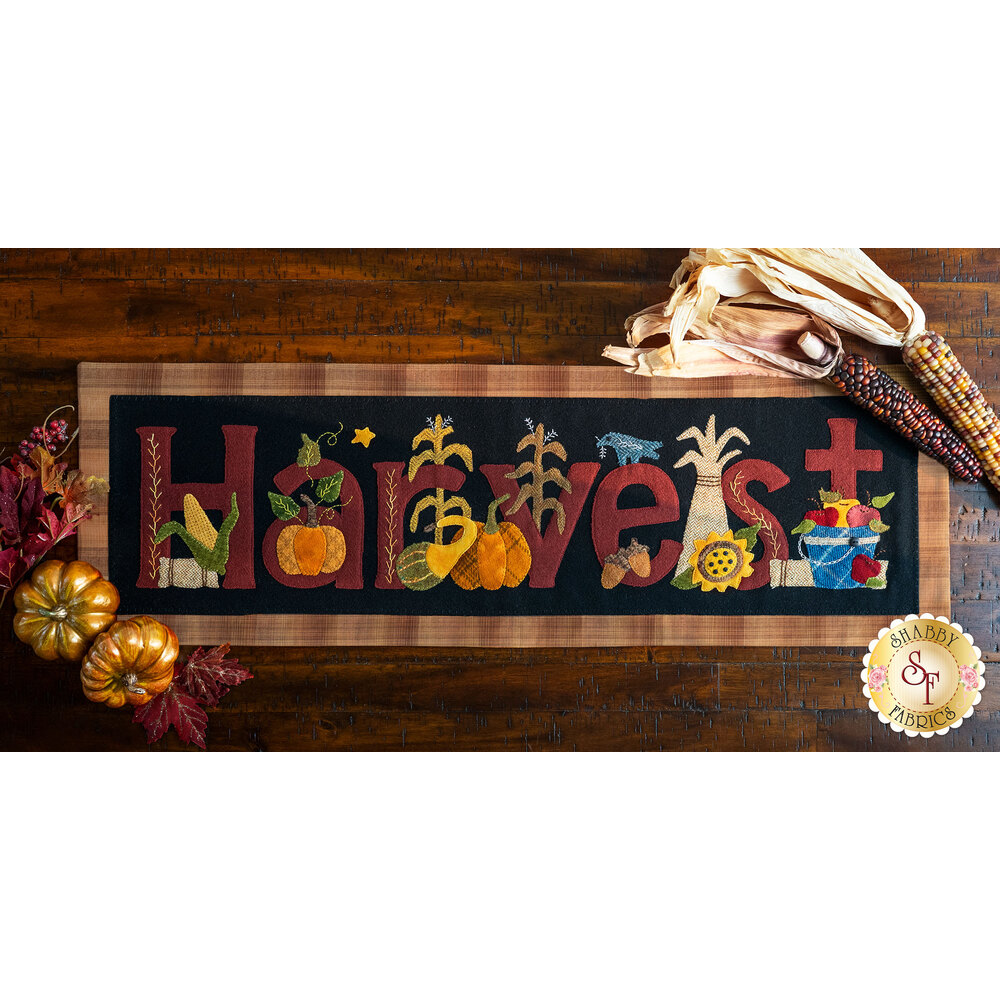 """Wool table runner with the applique word """"Harvest"""" displayed on a dark table"""