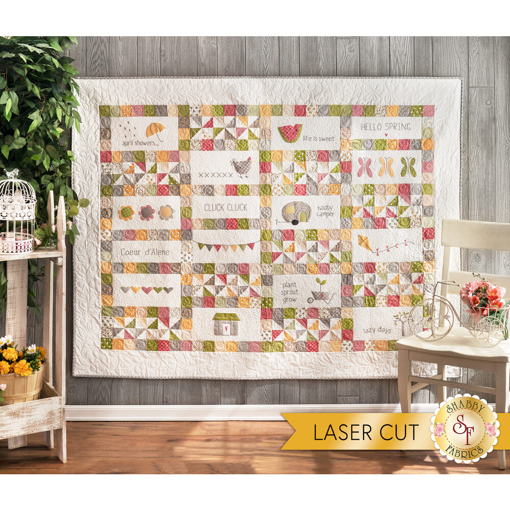 An adorable quilt with small square borders surrounding white embroidery blocks hung from a wall