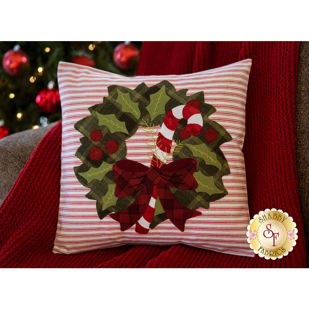 A Christmas pillow with holly and candy cane applique