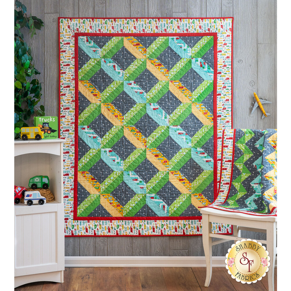 The On The Go Home & Away quilts hung from a wall and draped over a chair