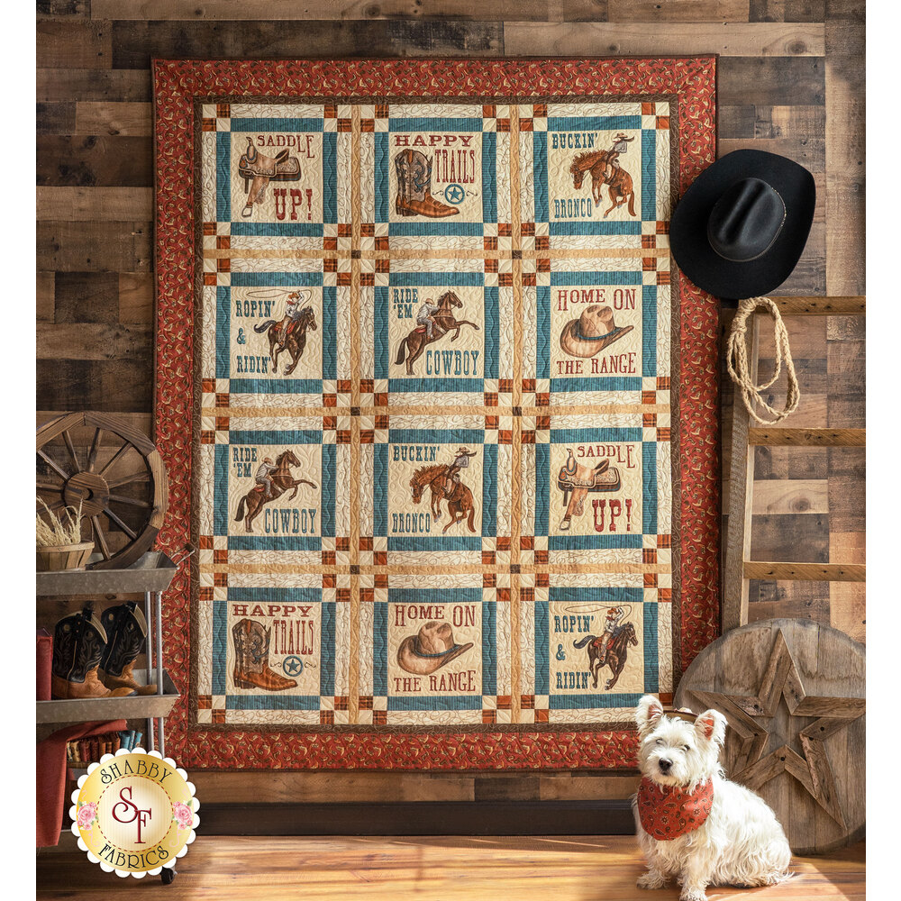 The beautiful Home On The Range Panel Quilt hung from a rustic wall