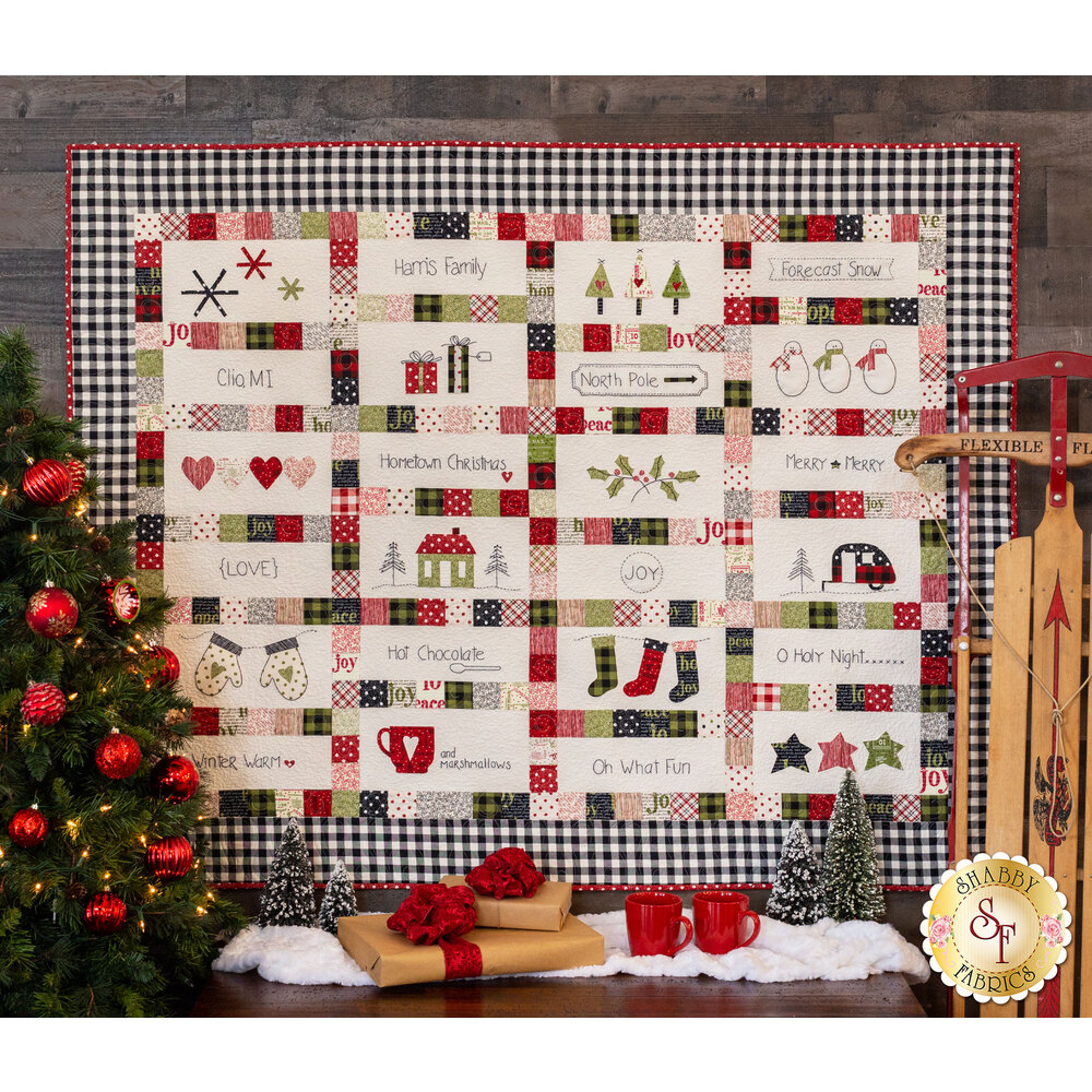 The finished Hometown Christmas Quilt displayed on a wall
