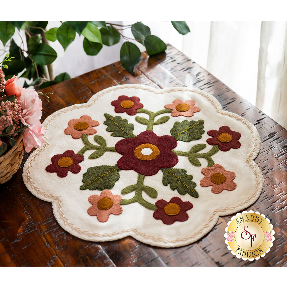 Adorable wool mat with appliqué flowers on a wood desk