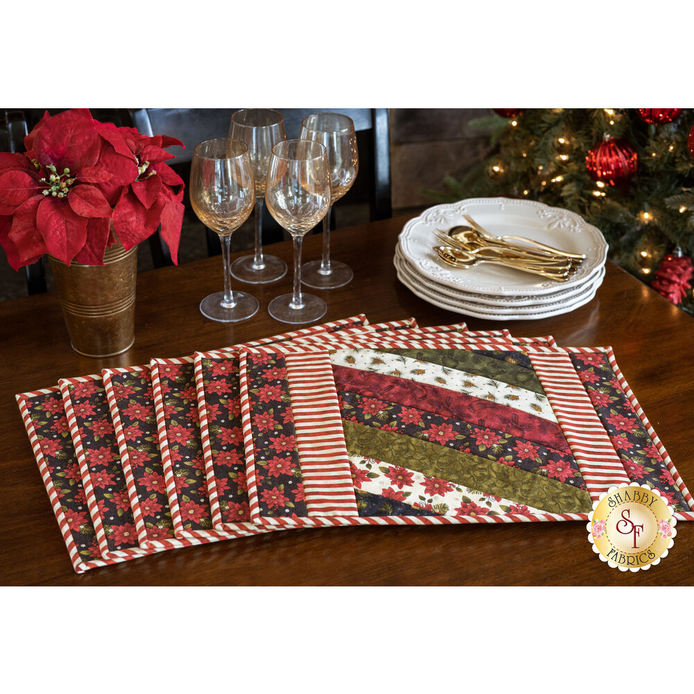 A stack of 6 Jakarta Placemats made with Winterberry fabrics on a dark wood table
