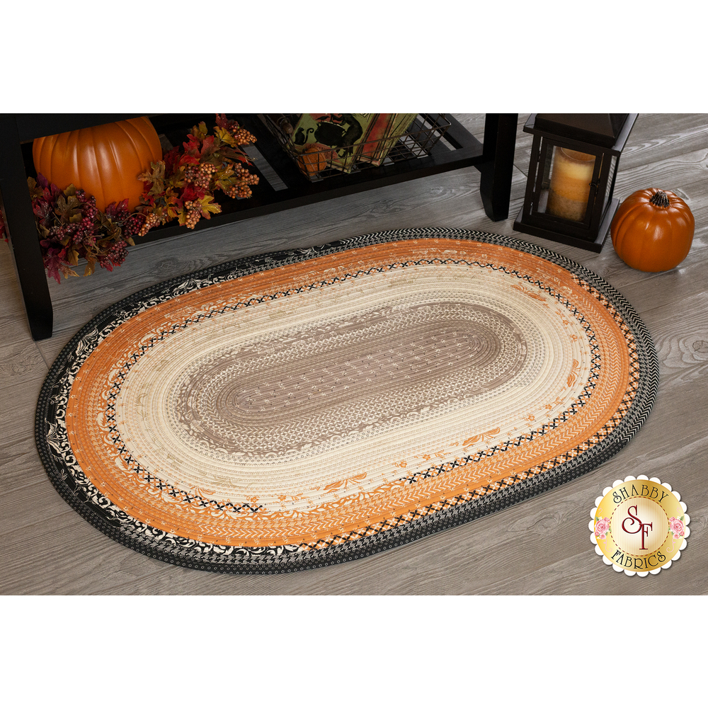 A black, orange, tan, and cream Jelly Roll Rug displayed on a wood floor