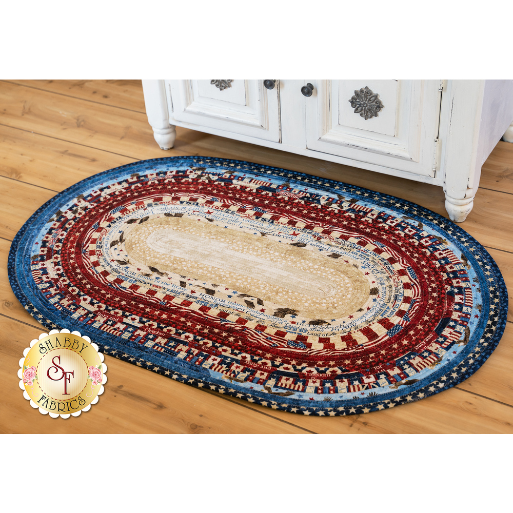 A detailed image of the Stars & Stripes 7 Jelly Roll Rug On a Hardwood Floor | Shabby Fabrics