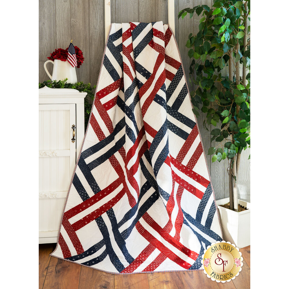 The beautiful Jelly Weave Quilt made with American Gathering fabrics draped over a ladder