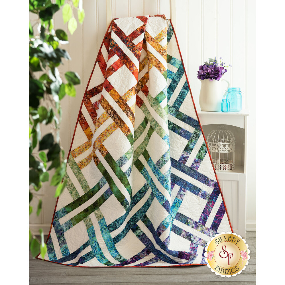 The beautiful Jelly Weave Quilt made with Floragraphix V fabrics draped over a ladder