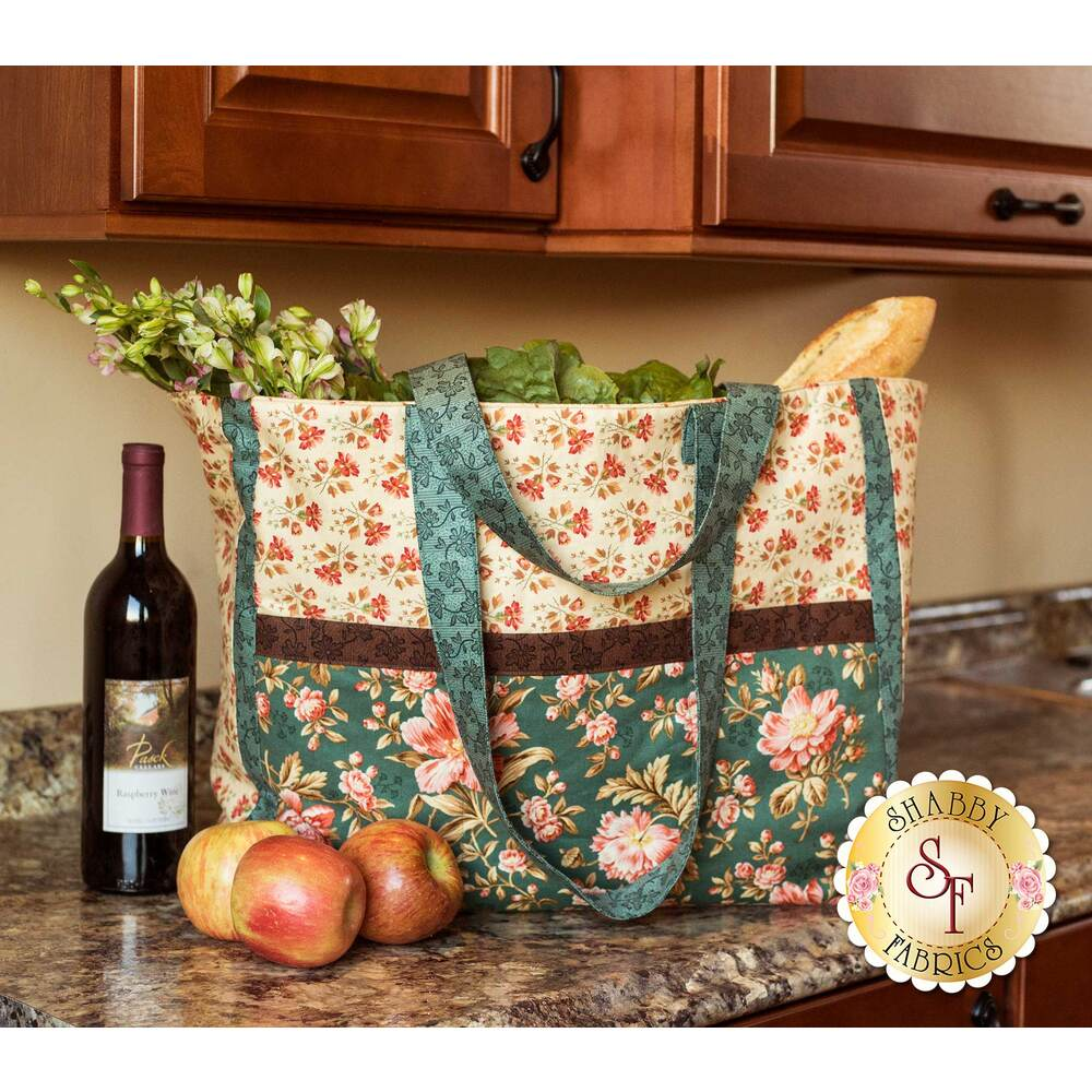 Large cream and teal floral fabric tote with baguettes, flowers, wine bottle, and groceries.