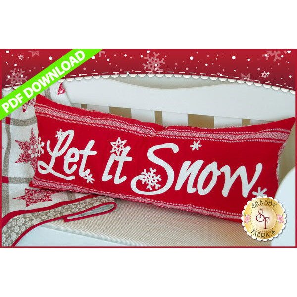 Red bench pillow with white appliqued wool text reading Let It Snow.