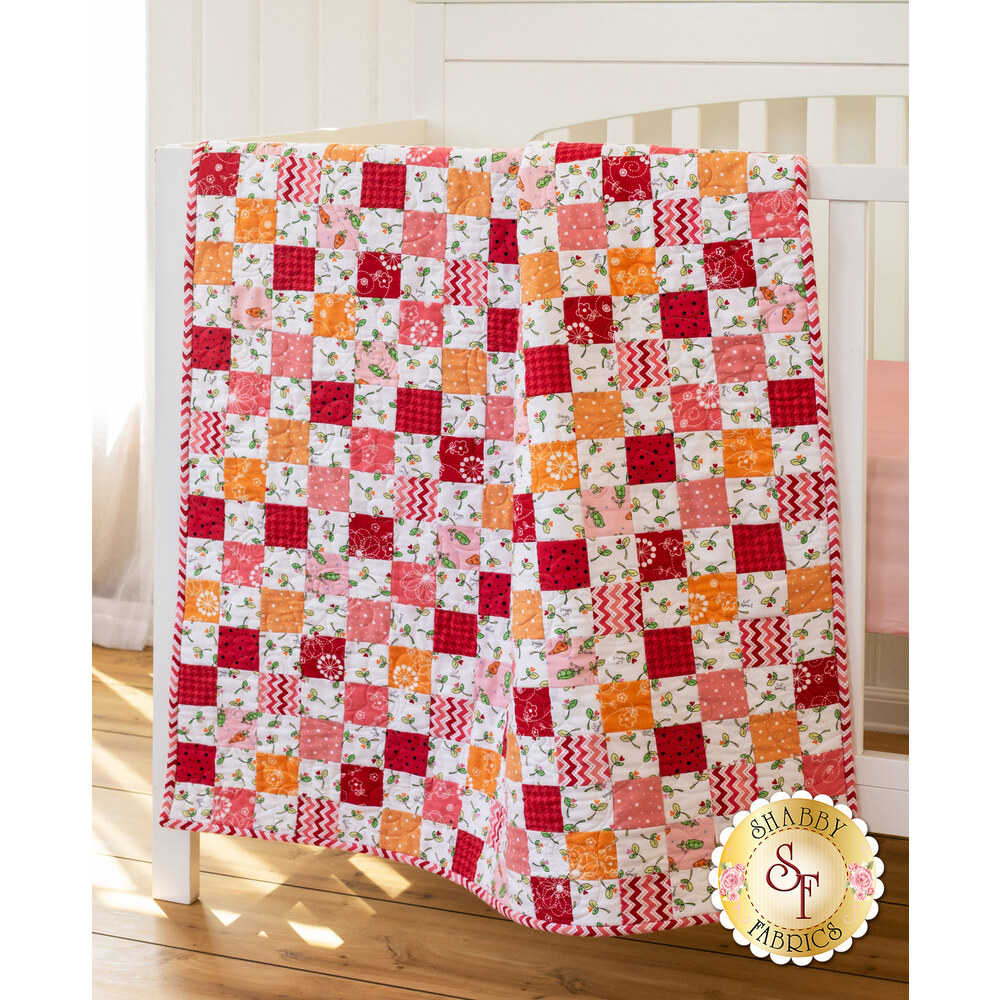 Pink, red, and orange flannel patchwork quilt with fun variegated prints.