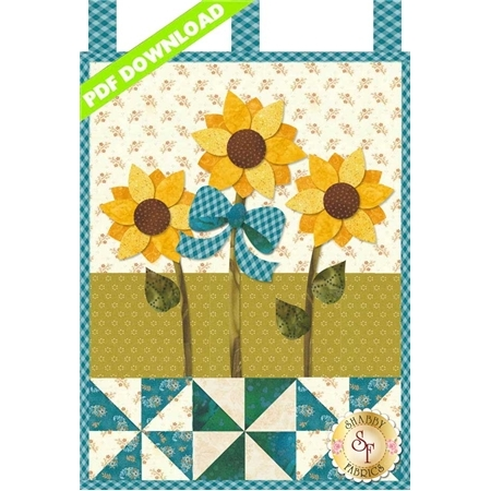 Three yellow sunflowers with a large teal ribbon and teal pinwheels.